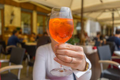 Blurred woman on background holding Aperol spritz in front of he Stock Images