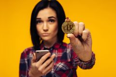 Blurred woman holding a Bitcoin in her hand and showing it. Image royalty free stock photo