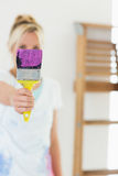 Blurred woman holding out paint brush at new house Stock Images