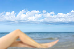 Blurred woman leg with blue sky and white cloud Royalty Free Stock Images