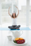 Blurred woman in meditation posture with healthy food in foreground Stock Photos