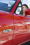 Blurred Woman In Red Electric Car Stock Image