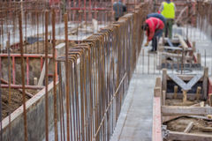 Blurred workers and steel reinforcement in foundation of  new bu Royalty Free Stock Photo