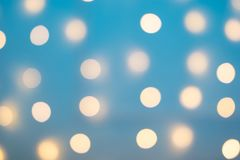 Blurred yellow balls on a blue background. Texture. Christmas garland. Blurry light yellow balloons on a blue background. Texture. Christmas garland stock photography