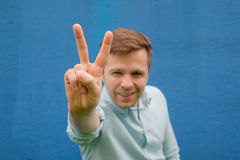 Blurred young man in blue shirt posing in blue background with hand showing the victory sign. And looking at the camera Stock Photography