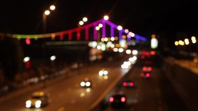 Blurring background of an evening city. View from the bridge on the evening city. Bridge in colorful lights. A shot for a background stock video
