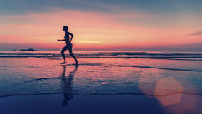 Blurring silhouette of running woman on the sea beach. Stock Image
