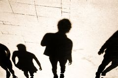 Blurrry shadow silhouete of  people walking in high contrast. Blurrry shadow silhouete of  people walking on pedestrian street in high contrast sepia  black and royalty free stock image