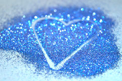 Blurry abstract background with heart of blue glitter sparkle on blue surface Stock Images
