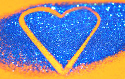 Blurry abstract background with heart of blue glitter sparkle on orange surface. Blurry background with heart of blue glitter sparkle on orange surface Royalty Free Stock Photography