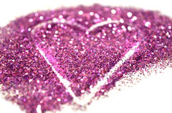 Blurry abstract background with heart of purple glitter sparkle on white surface Stock Images