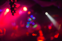 Blurry abstract colorful colored background in night club with bokeh red lasers Stock Photos