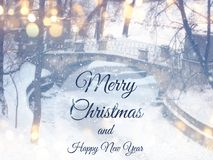 Blurry and abstract magical winter landscape photo with greeting text: Merry Christmas and happy new year. Glitter overlay Royalty Free Stock Photography
