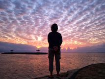 Free Blurry Background Of Young Woman Standing Looking At The Dramatic Sky Over The Sea. Stock Photography - 159304282