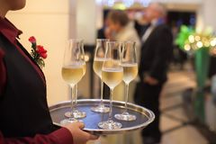 Blurry background waiter serving champagne to customer. In restaurant royalty free stock photography