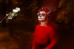 Blurry body and red lantern.with a painted face of a skeleton, a dead zombie, in the city during the day. day of all souls, day of royalty free stock photos