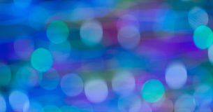 Blurred bokeh in blue shades with green and purple. Blurry bokeh in blue shades stock photography