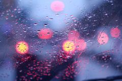 Blurry bokeh and raindrops on car window after the rain stock images
