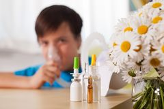 Blurry boy using inhaler device with medication in the foreground. Allergy and asthma treatment concept royalty free stock photos