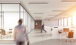 Blurry business man walking inwhite  office interior. Blurry business men walking inwhite  office interior with sunlight. Woman on background. Law office Stock Image