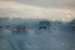 Blurry car silhouette seen through water drops on the car windshield stock photography