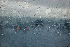 Blurry car silhouette seen through water drops on the car windshield royalty free stock photography