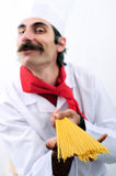 Blurry Chef showing spagetti. And  smiling Royalty Free Stock Photos