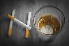 Blurry cigarettes and glass of alcohol forming the word NO Stock Images
