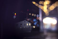 Blurry city lights, streets with Christmas decorations. Night city, blurry bokeh lights, houseswith light in the windows Royalty Free Stock Photography