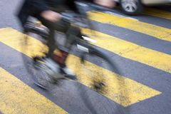 Blurry cyclist on city street. Blurry urban cyclist on yellow zebra crossing on city street Royalty Free Stock Images