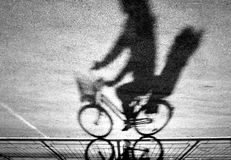 Blurry cyclist silhouette and shadow royalty free stock photos