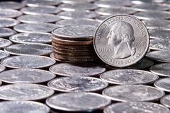 Blurry dice rolled over silver US currency quarters in a uniform pattern 1 stock photo
