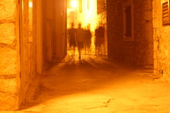 Blurry figures in alley. A yellow-tone night view of fuzzy or blurred figures of people walking in an old alley in Croatia. Atmosphere of mystique or ghosts royalty free stock image