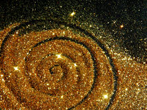 Blurry golden spiral of glitter sparkle on black background Stock Photos