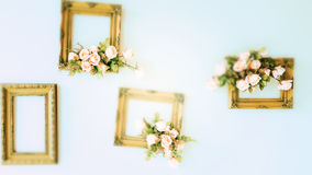 Blurry Golden Wooden frame with flowers on the wall. Stock Image