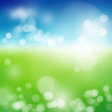 Blurry green field and blue sky with summer sun burst.  Royalty Free Stock Photography