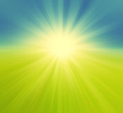 Blurry green field and blue sky with summer sun burst, retro bac Royalty Free Stock Photography