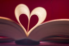 Blurry heart made from book pages over red background Stock Photos