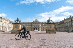 Blurry image of man cycling past large cobblestone courtyayd sur. STUTTGART, GERMANY - SEPTEMBER 13 2017; Blurry image of man cycling past large cobblestone Stock Photos