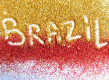 Blurry inscription Brazil on golden and red glitter sparkles on white background Stock Image