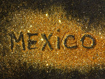 Blurry inscription Mexico on golden glitter sparkle on black background Royalty Free Stock Image