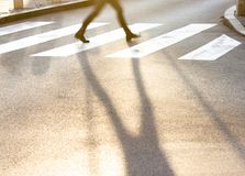 Blurry legs and shadow of a teenage girl crossing the city stree. Blurry legs and shadow of a teenage girl crossing the small city street at sunset in a hurry Royalty Free Stock Image