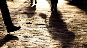 Blurry legs  silhouettes and shadows of people walking in sunset. Blurry legs  silhouettes and shadows of people walking on city patterned square in sunset Royalty Free Stock Photography
