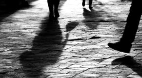 Blurry legs silhouettes and shadows of people walking in sunset stock images