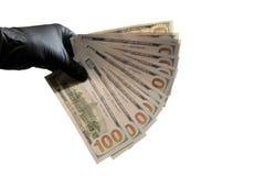 blurry A mão esquerda em uma luva preta guarda notas de dólar Fundo branco Copie o espaço fotos de stock royalty free