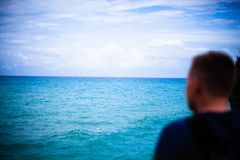 Blurry Man looking the horizont from a cliff. Tourist ovelooking the open sea. Waves shoaling and approcahing the seabed.Relaxing stock photo