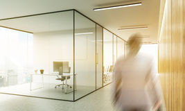 Blurry man in office. Side view of blurry businessman walking in office interior with blank whiteboard behind glass doors and hallway with wooden wall, New York Stock Photo