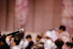 Blurry of microphone in auditorium and projector for shareholders ` meeting stock photography
