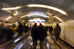 Blurry motion image of people walking. Horizontal escalators in subway station in Paris. Sortie means exit in French stock images