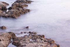 Blurry ocean between rocks Royalty Free Stock Photos